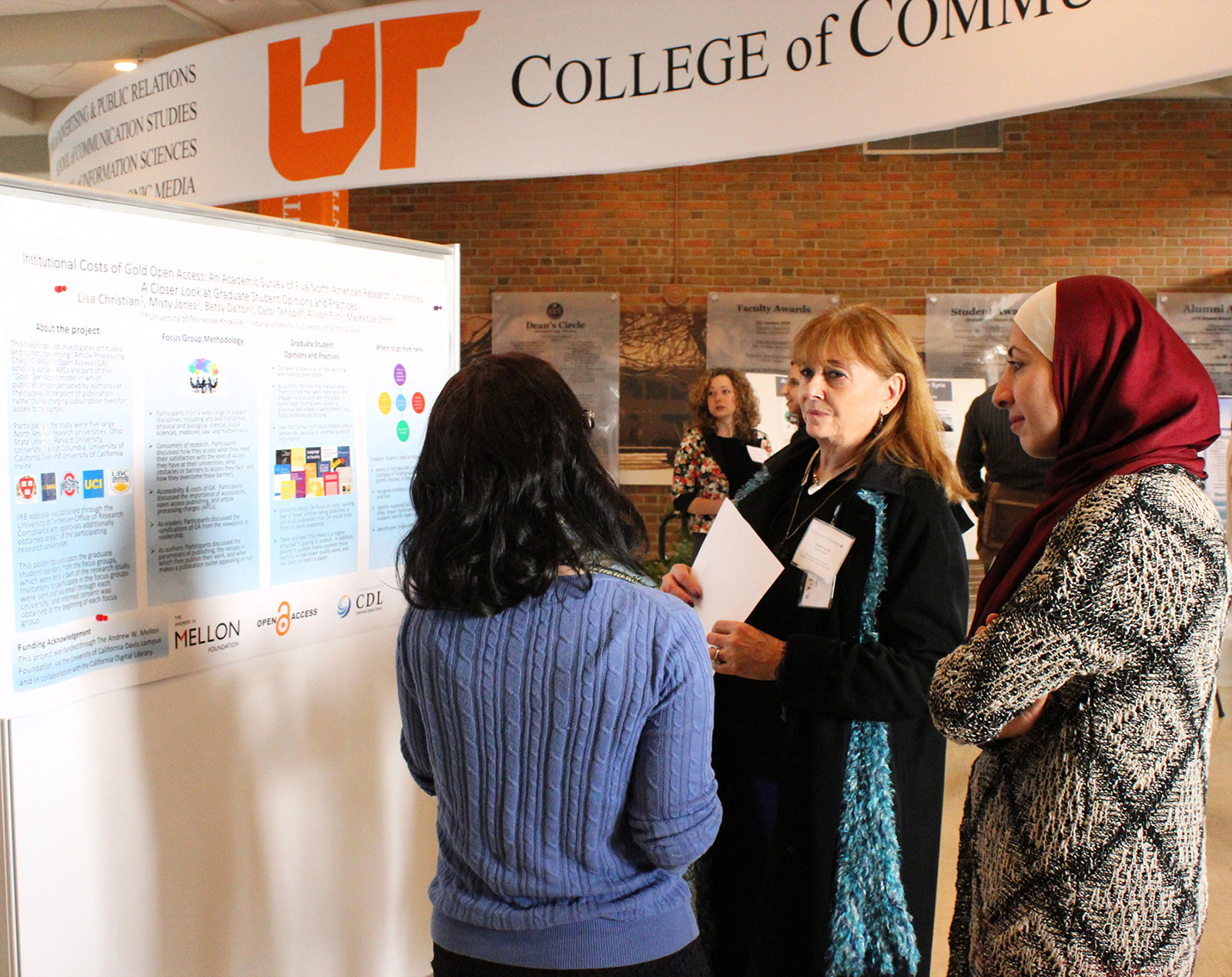 Bonnie Carroll, BOV member and SIS student Suzan Ali Saleh listen to another poster presenter explain her research.